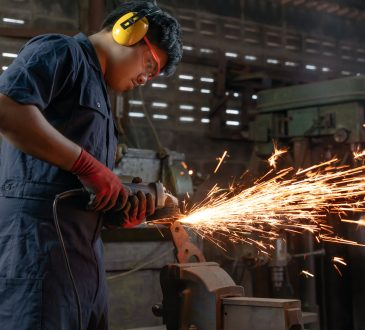 Engineer operating angle grinder hand tools in manufacturing factory - Mechanical engineering student using power tool with hot metal sparks wearing safety equipment - workshop and occupation concept