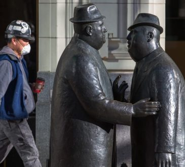 A worker wears a mask as he walks past the well-known statues of two businessman talking in downtown Calgary on Tuesday, March 17, 2020