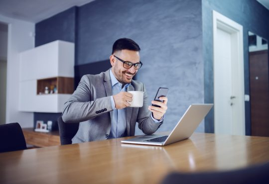 businessman looking at smartphone at home
