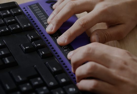 blind person using braille keyboard