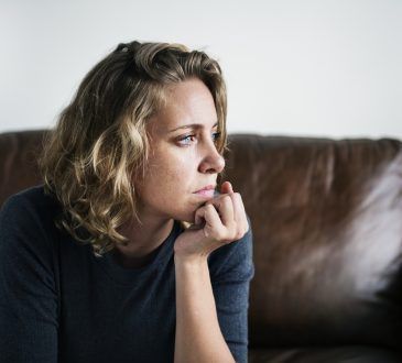 worried woman sitting on couch