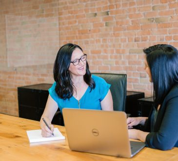 two women talking at table in office