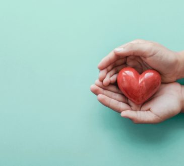 hands holding red heart on blue background