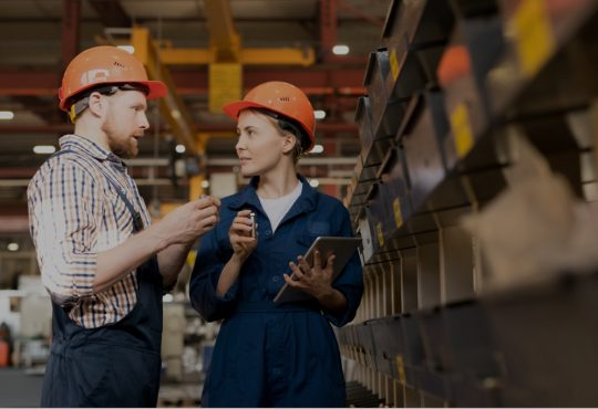 two people wearing hard hats in warehouse