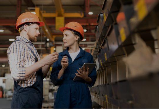 two people wearing hard hats in warehouse