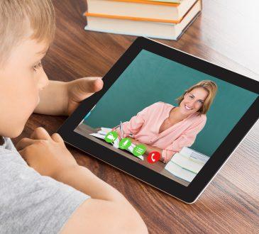 Boy Videoconferencing On Digital Tablet In Classroom