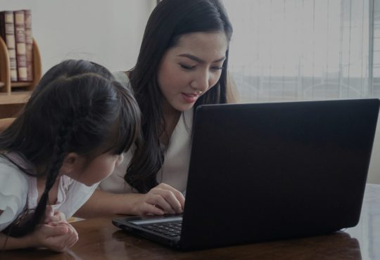 mom working while daughter looks on