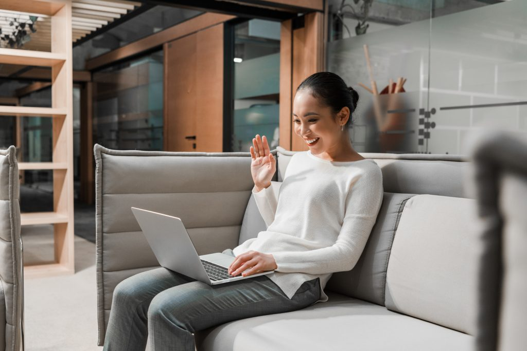 woman sitting on couch having video call