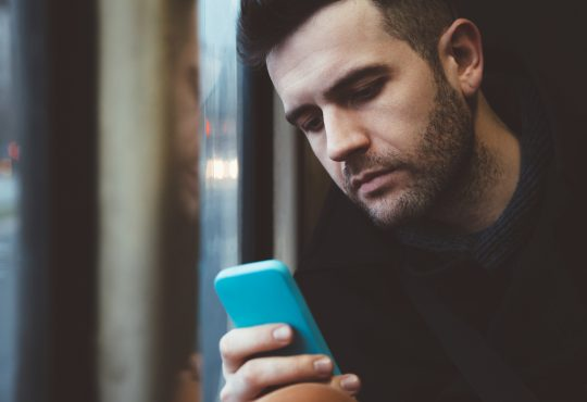 man looking at phone worried