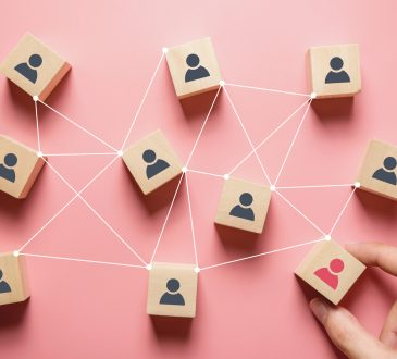Wooden blocks with people icon on pink background, Human resources and management concept.