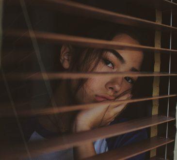 woman looking through blind slats looking worried