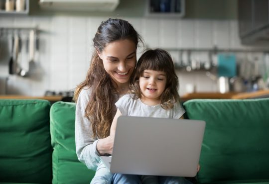 mom and young daughter using laptop together