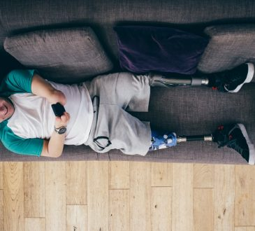 man with prosthetic legs lying on couch
