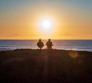 two people sitting and looking at sunset