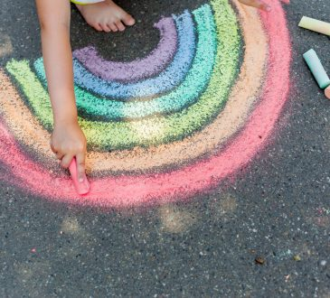 kid drawing chalk rainbow