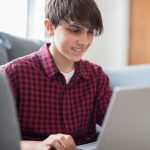 Teenage Boy Working On Laptop At Home