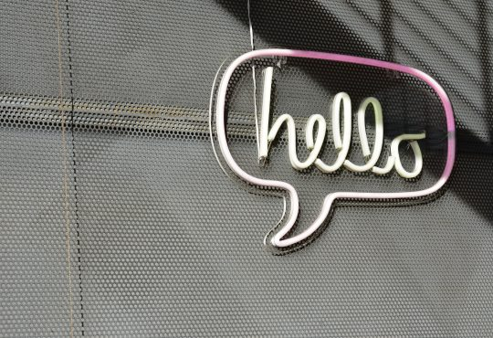 "neon ""hello"" sign on grey background"