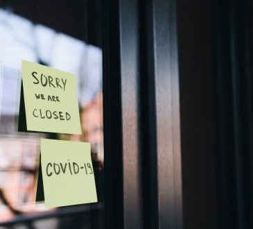 "sticky note reading ""sorry we are closed. COVID-19"" on door"
