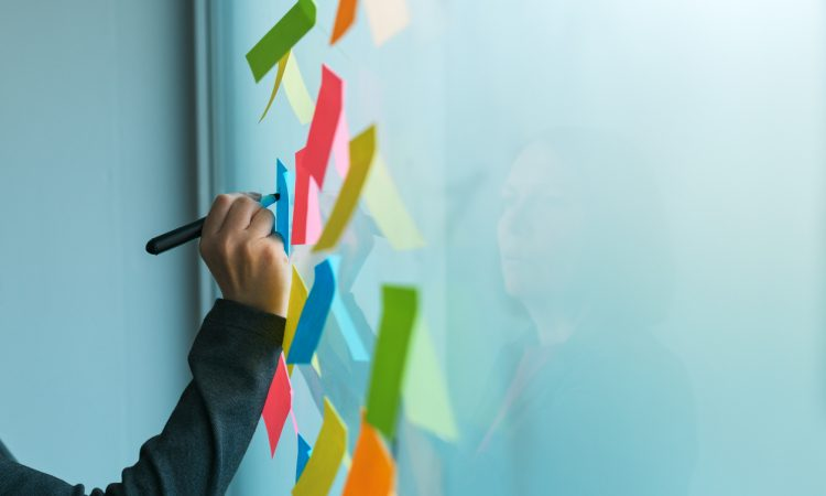 Businesswoman writing on colorful sticky note paper