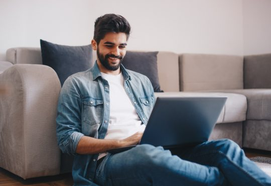 Young relaxed man working on laptop while sitting on floor at home