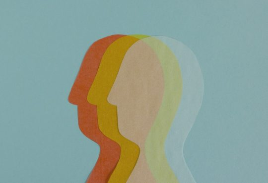 Composed row of transparent paper cutout of heads overlapped on blue background