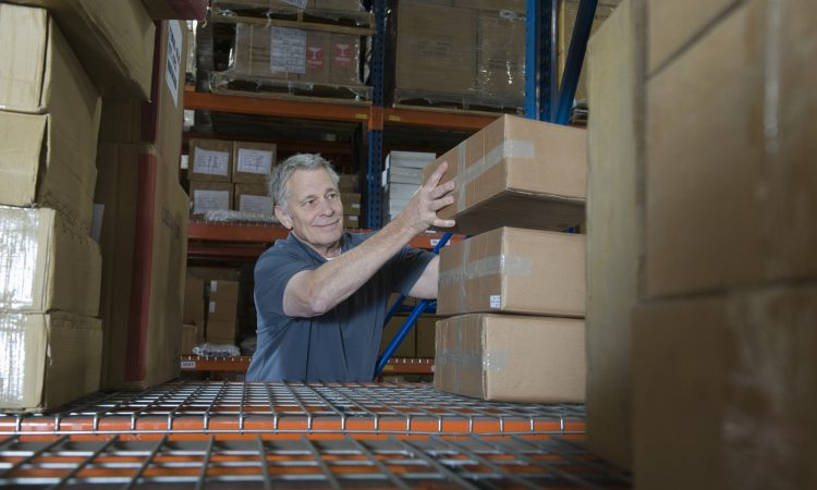 Smiling middle aged man stacking boxes in distribution warehouse