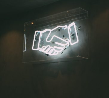 neon sign of shaking hands