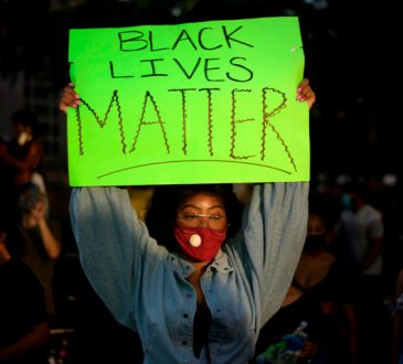 woman holding up Black Lives Matter sign at protest