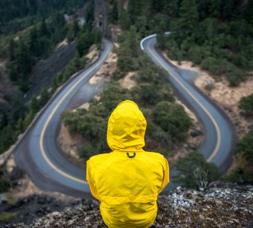 person in yellow coat sitting on hill overlooking winding road
