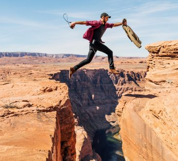 man jumping from rock to rock over canyon