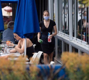 waitress on restaurant patio wearing mask