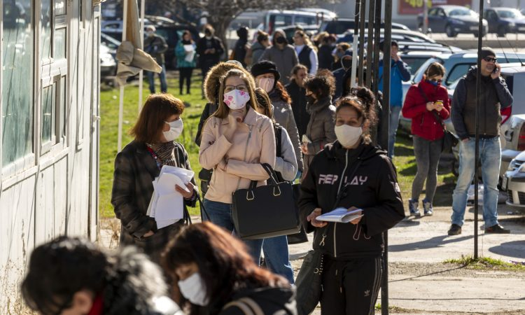 People wearing face masks in an attempt to prevent the spread of coronavirus disease COVID-19 wait in line in front of an office of the labor bureau.