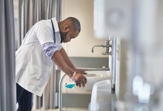 male doctor holding on to edges of sink with head bent down