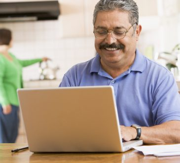 Man in kitchen with laptop smiling with woman in background