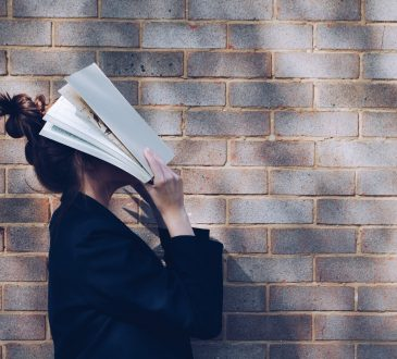 student covering face with book
