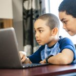 two boys using laptop