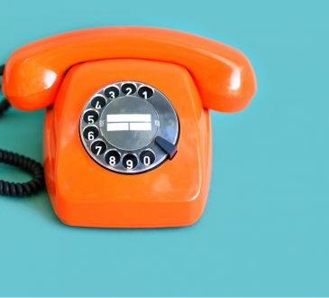 orange rotary phone on blue background