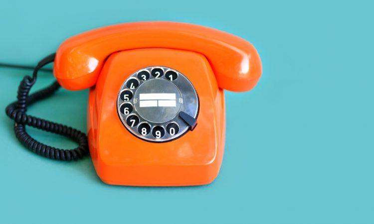 orange rotary phone on blue background
