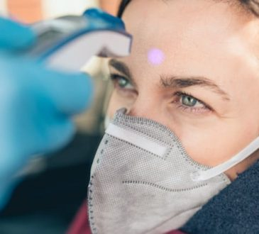 closeup of person having temperature checked with no-contact machine on forehead