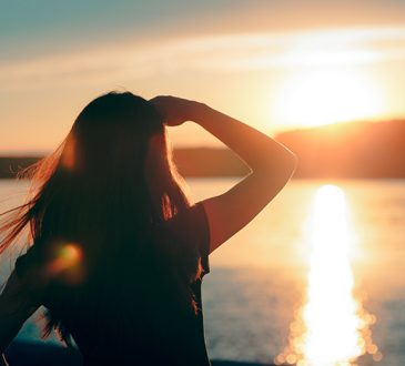 woman watching sun set over water