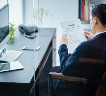 businessman reviews resume in office