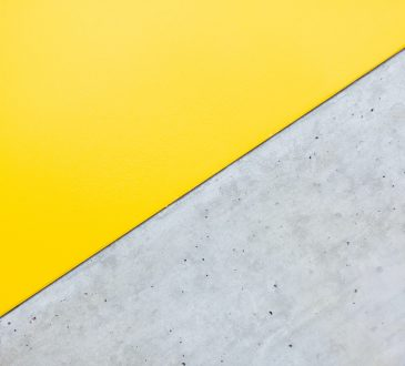 rectangle divided on vertical line with concrete on one side and bright yellow on other