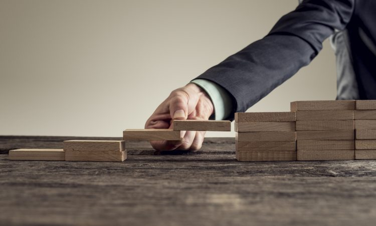 businessman forming a bridge of wooden building blocks in a gap in a set or steps