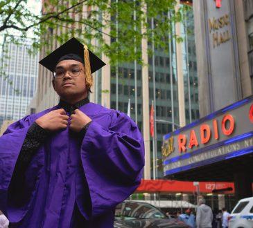 male university graduate wearing purple robe and cap on city street