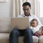 Father working from home and taking care of baby