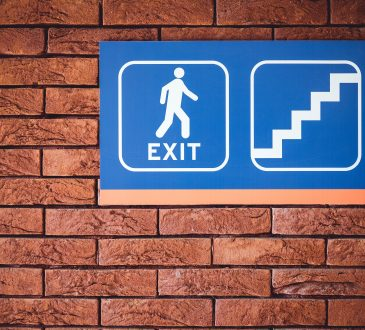 blue exit sign on brick wall