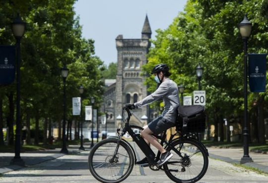 A cyclist rides past the University of Toronto campus during the COVID-19 pandemic in Toronto.