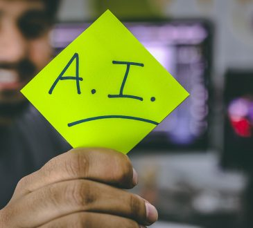 """man holding up sticky note that says """"AI"""""""