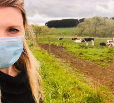 woman standing in field wearing mask