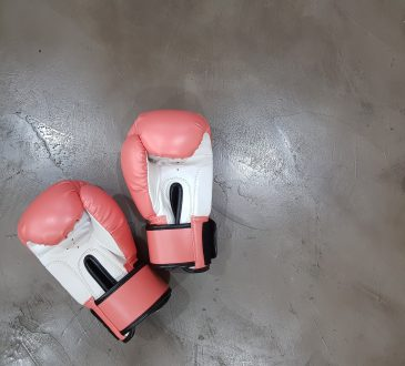 two pink and white boxing gloves on concrete floor